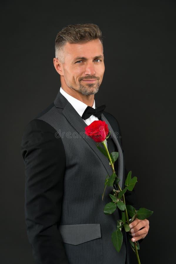 愉快的妇女的天 拿着红色玫瑰的典雅的人在womes天 正装和黑bowtie庆祝的帅哥 免版税库存图片