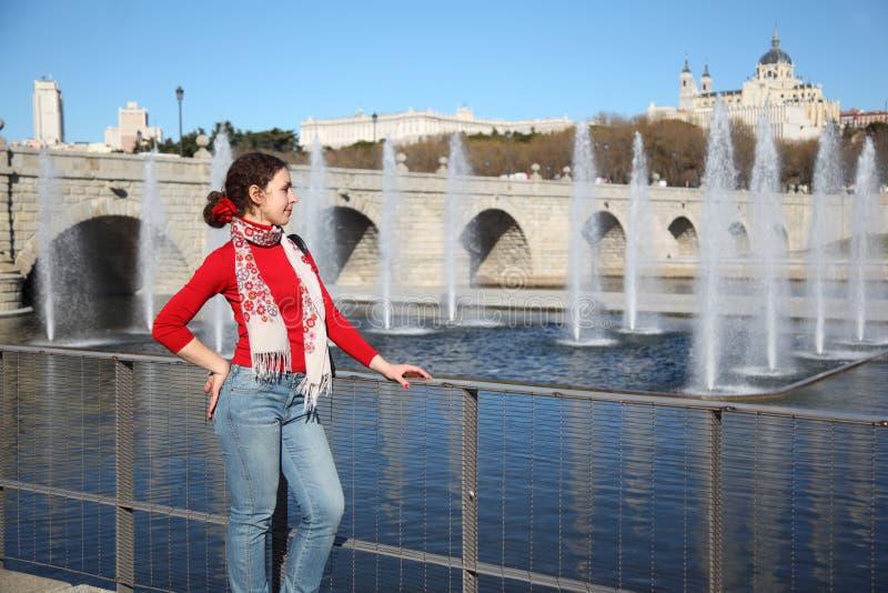 年轻愉快的妇女站立近的桥梁 免版税库存照片