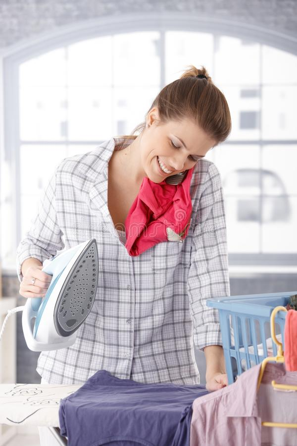 愉快的妇女联系在电话,当电烙时 免版税库存照片