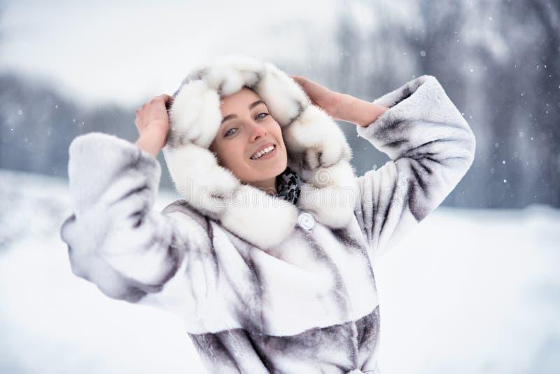 愉快的妇女获得在雪的乐趣在冬天森林 免版税库存照片