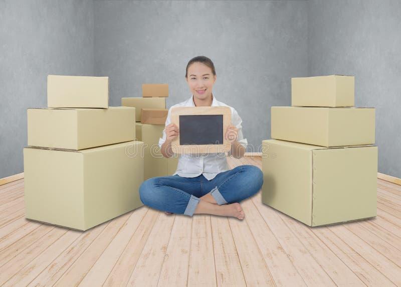 愉快的妇女藏品黑板、企业交付对象到新的家里或办公室 图库摄影