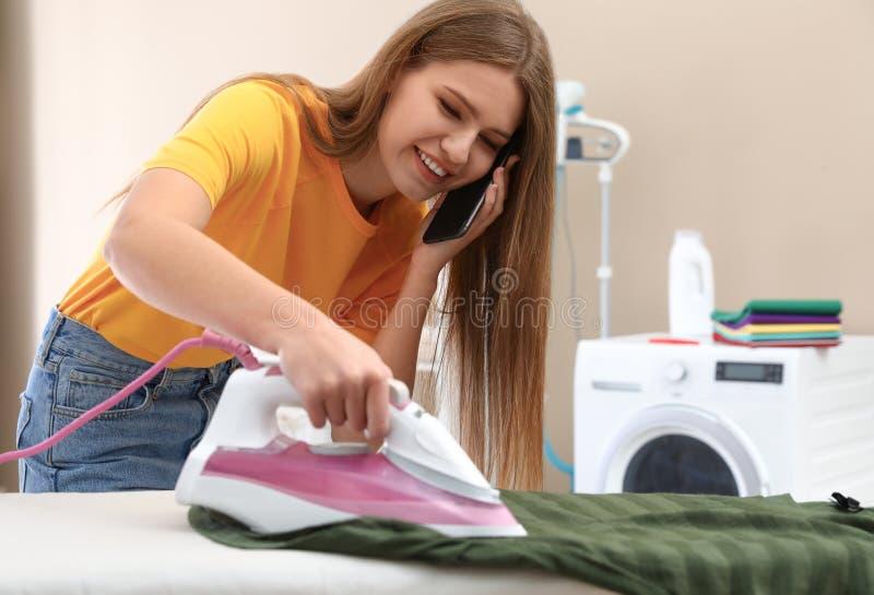 愉快的妇女谈话在电话,当电烙衣裳在卫生间里时 免版税图库摄影