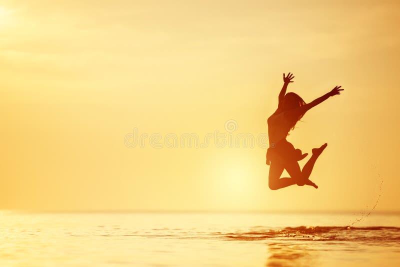愉快的妇女跳湖水日落 图库摄影