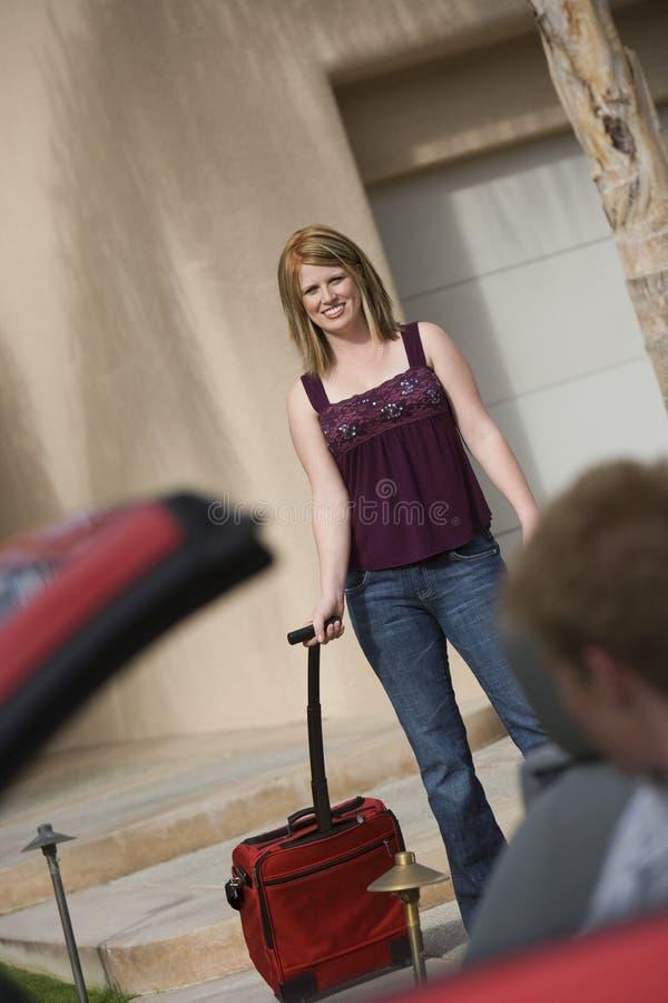 愉快的妇女运载的行李 免版税库存照片
