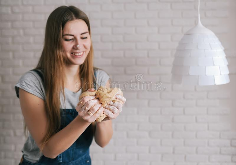 愉快的妇女面包师揉面团团以砖墙和白色灯为背景 图库摄影