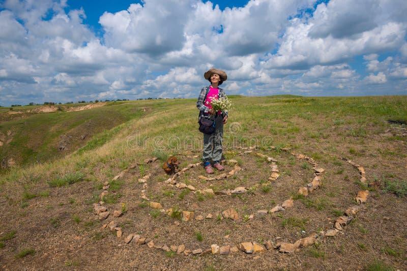 愉快的妇女,有小滑稽的狗的,在大草原站立 免版税库存照片