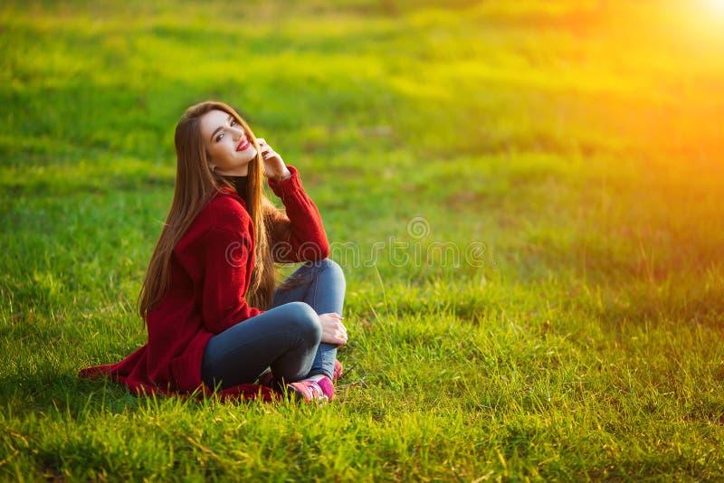 愉快的妇女年轻人 有长的健康头发的美丽的女性享受太阳光的在公园坐绿草 春天 免版税库存图片