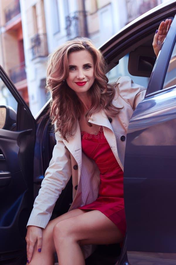 愉快的妇女 坐在汽车的一名美丽的微笑的妇女的室外画象 库存图片