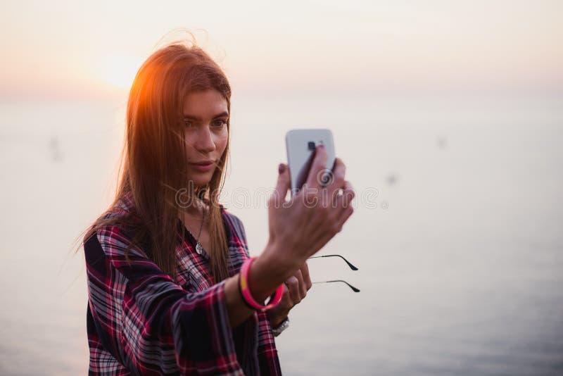年轻愉快的妇女画象站立在美丽如画的海视图前面的行家衬衣的,采取与日落的selfie或 库存图片