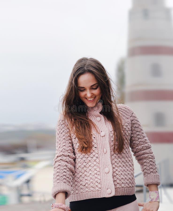年轻愉快的妇女画象,看下来和微笑,在逗人喜爱的柔和的桃红色毛线衣,秋天时尚穿戴了 免版税图库摄影