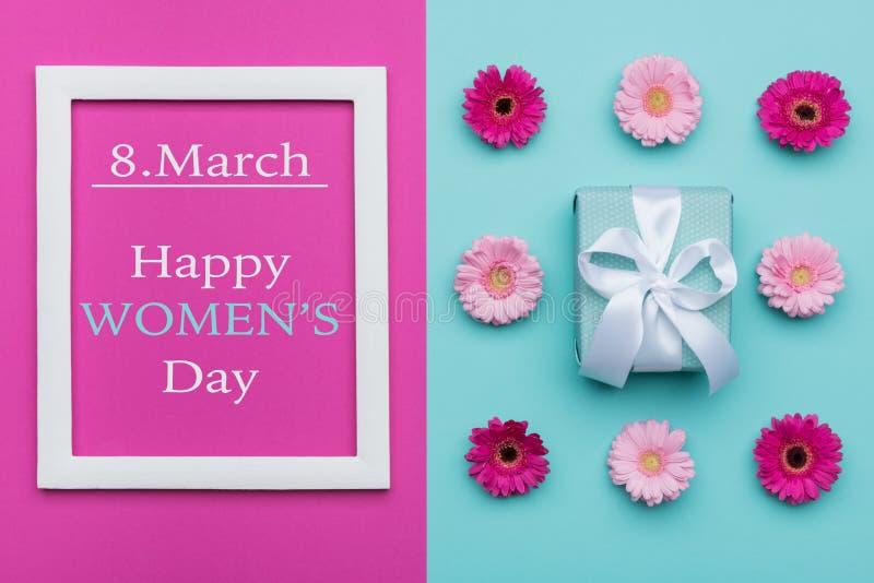 愉快的妇女` s天淡色糖果上色背景 花卉与美妙地被包裹的礼物的妇女的天平的位置 免版税库存照片