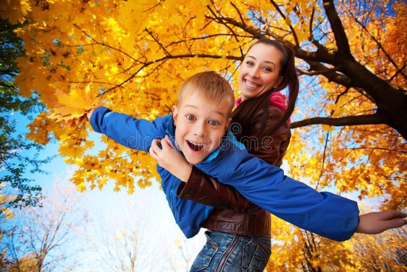 愉快的妈妈和儿子充当秋天公园 免版税库存图片