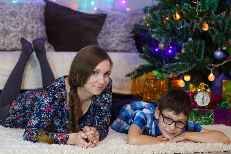 愉快的妈妈和儿子在白色地毯、新年心情、圣诞树和礼物在家说谎 免版税库存照片