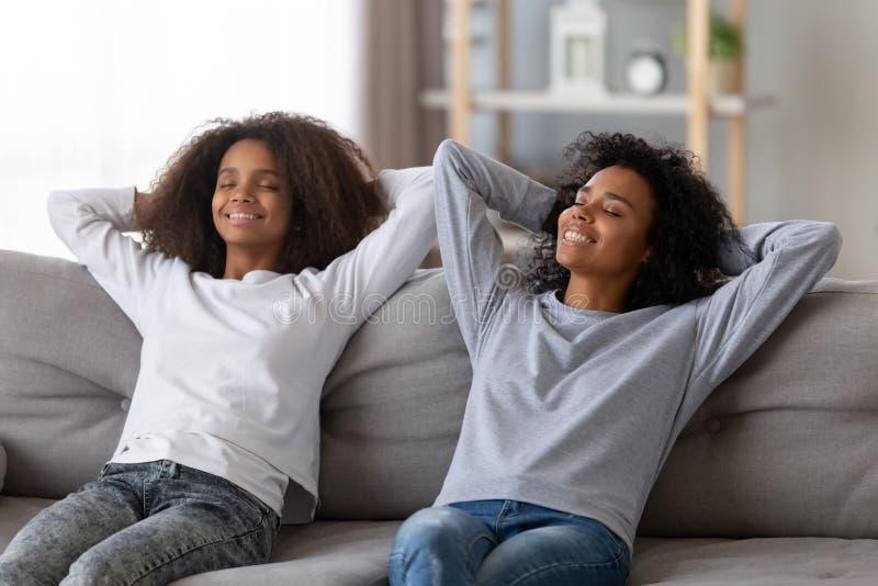 愉快的妈妈和女儿放松在长沙发的手天花板 图库摄影