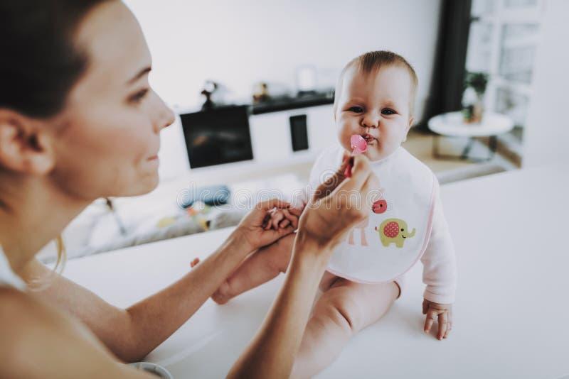 愉快的妈妈喂养有匙子的可爱的婴孩户内 图库摄影