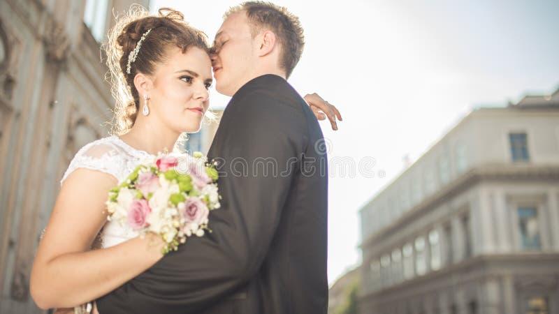 年轻愉快的婚礼夫妇新娘在一婚礼之日遇见新郎 大阳台的愉快的新婚佳偶有出色的意见 图库摄影
