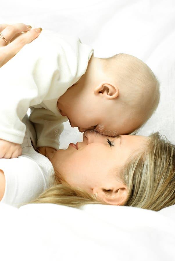 愉快的婴孩她的母亲沙发 库存图片
