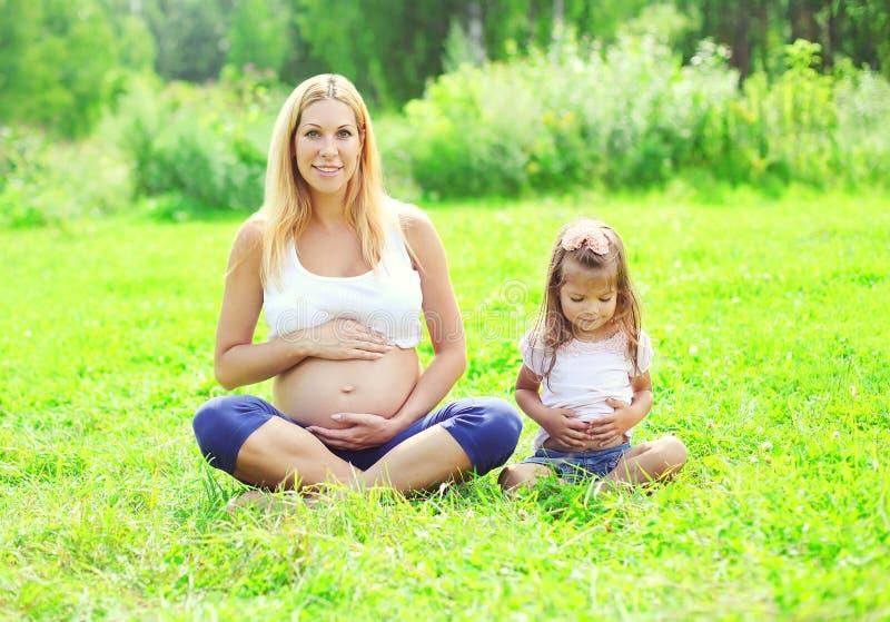 愉快的孕妇、母亲和小女儿孩子坐做瑜伽的草在夏天行使 库存照片