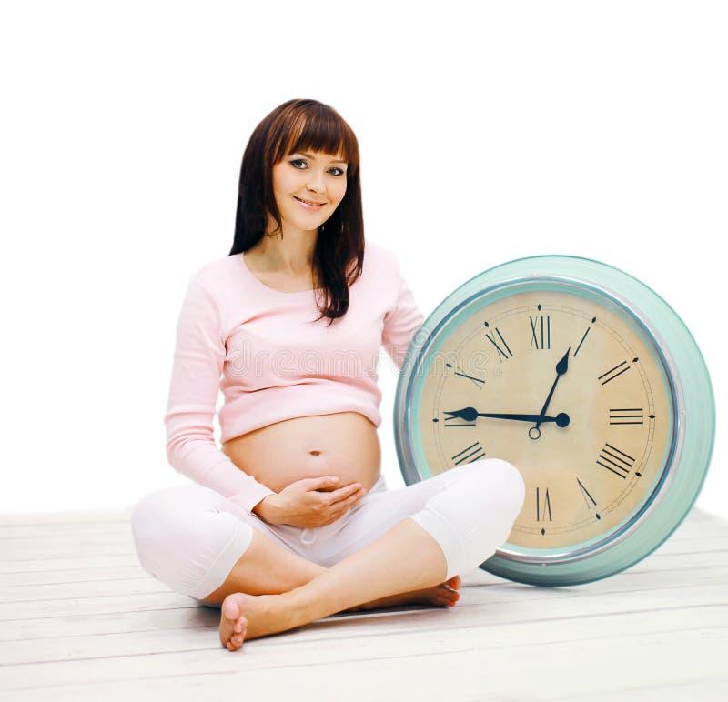 愉快的孕妇坐与一个大时钟的地板 库存照片
