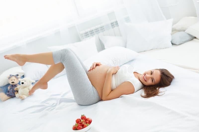 愉快的孕妇感到健康并且得到一些乐趣 健康fo 免版税库存照片