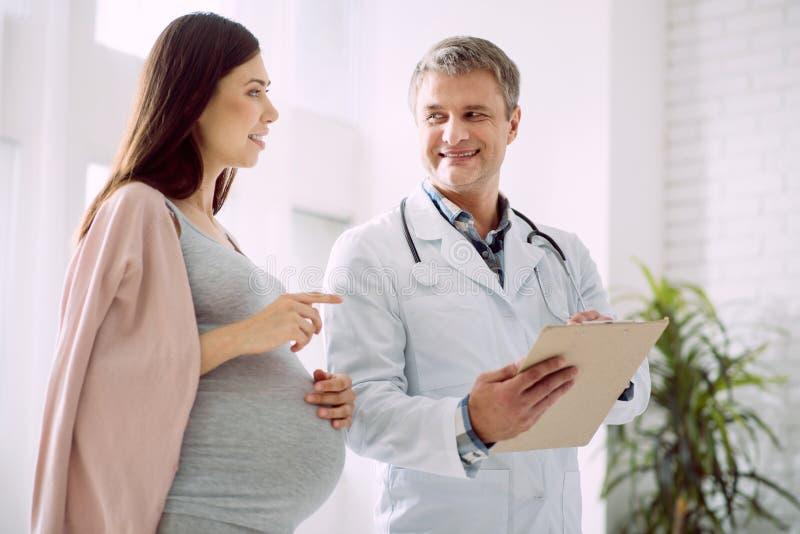 愉快的孕妇谈话与她的医生 库存图片