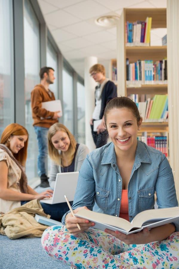 愉快的学生在学校图书馆里 库存照片