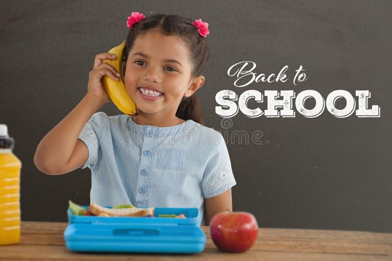 愉快的学生女孩在拿着电话的桌上反对有回到学校课文的灰色黑板 皇族释放例证