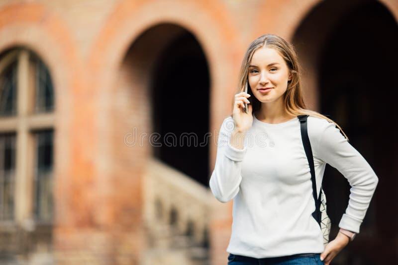 愉快的学生女孩讲的机动性户外在大学附近 库存图片