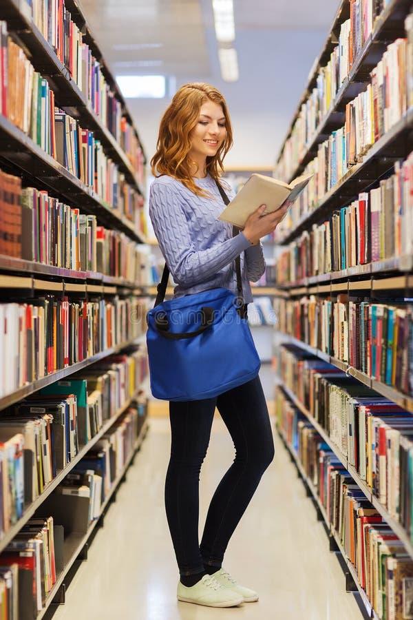 愉快的学生女孩阅读书在图书馆里 免版税库存图片