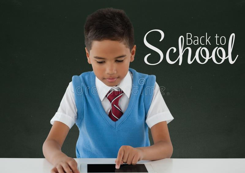 愉快的学生男孩在使用一种片剂的桌上反对有回到学校课文的绿色黑板 皇族释放例证