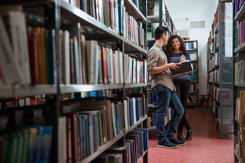 愉快的学生谈话在图书馆里 免版税库存照片