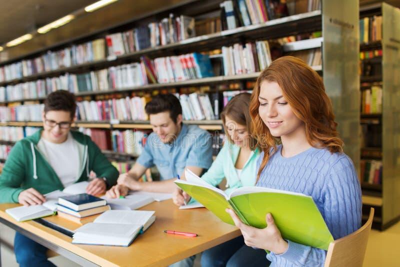 愉快的学生阅读书在图书馆里 库存照片