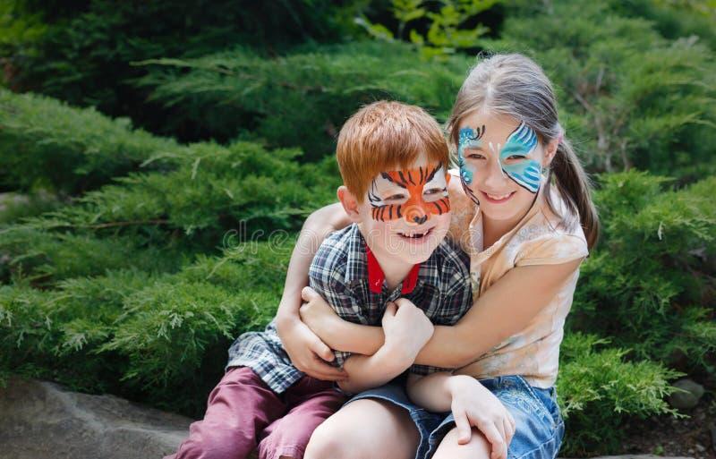 愉快的孩子、男孩和女孩有面孔油漆的在公园 库存图片