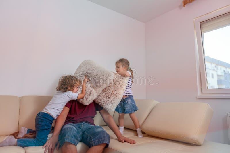 愉快的孩子一起使用与人的男孩和女孩在家 图库摄影