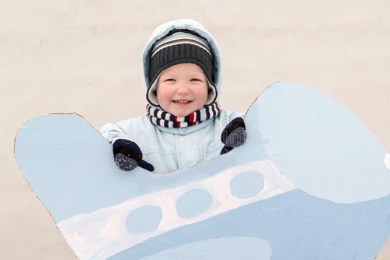 愉快的孩子以冬天时尚在他的村庄房子庭院给摆在与玩具飞机穿衣 第一雪,家庭, tradit 库存图片