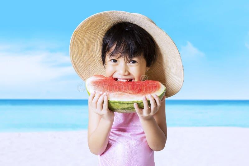 愉快的孩子吃西瓜在海岸 图库摄影