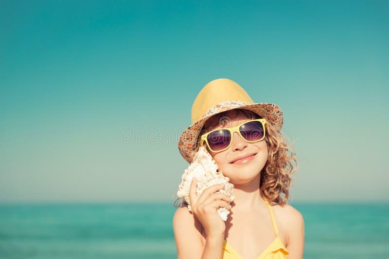愉快的孩子听在海滩的贝壳 库存照片