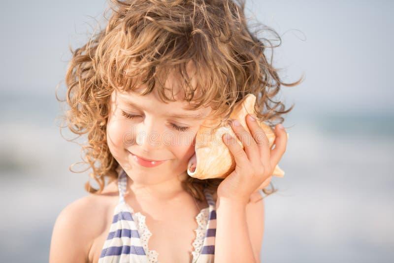 愉快的孩子听贝壳在海滩 免版税库存照片