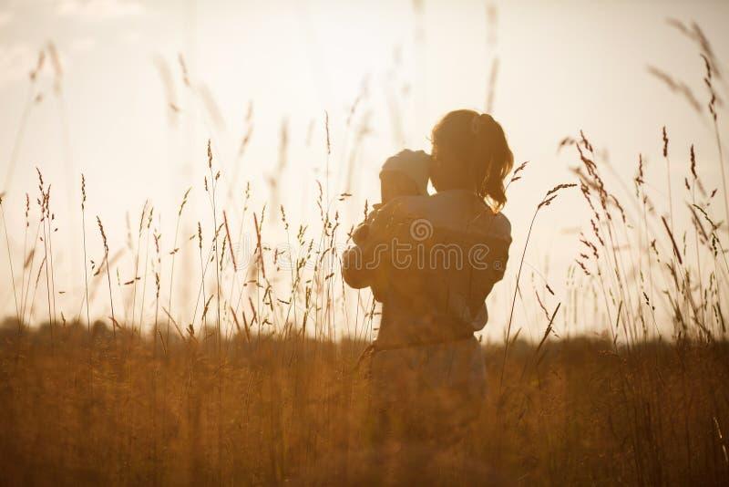愉快的孩子和他的妈妈获得乐趣户外在领域充斥与阳光 免版税库存照片