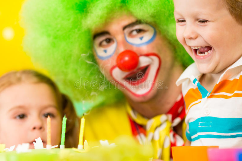 愉快的孩子和在蛋糕的小丑吹的蜡烛 免版税库存照片