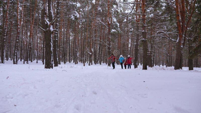 愉快的孩子和妈妈和爸爸奔跑与孩子冬天森林父母的使用与孩子在一个多雪的公园 库存照片