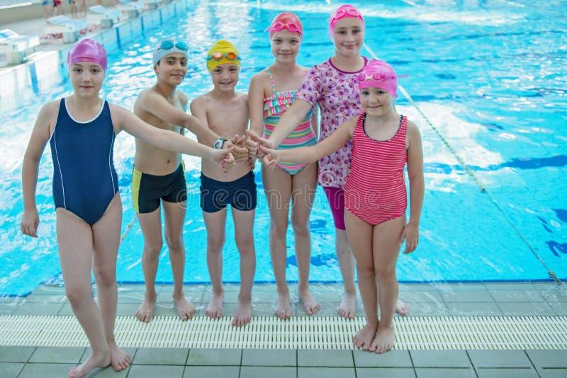 愉快的孩子哄骗小组在学会游泳池的类游泳 免版税库存图片