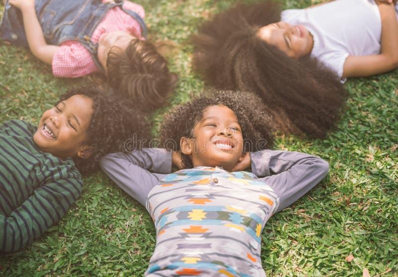 愉快的孩子在公园哄骗放置在草 免版税库存照片