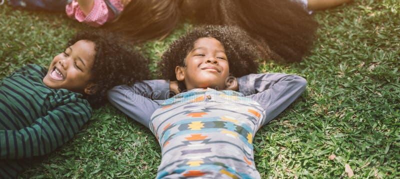 愉快的孩子在公园哄骗放置在草 免版税库存图片