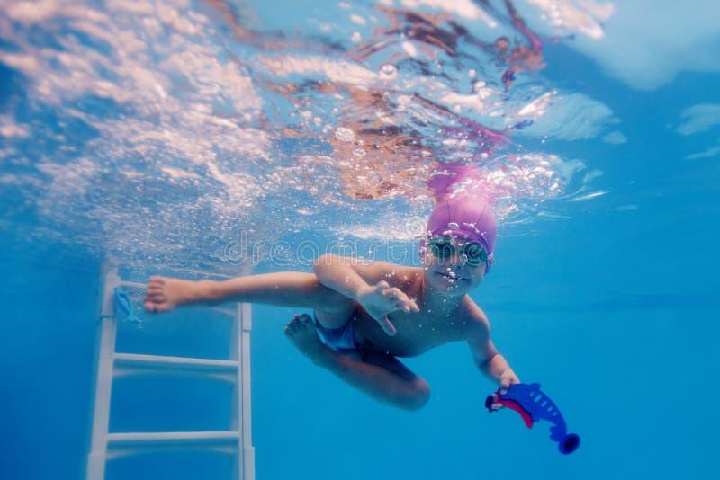 愉快的孩子在水池被训练潜水 图库摄影