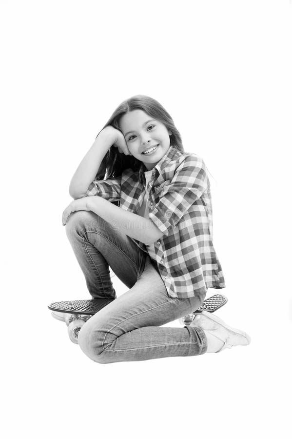 愉快的孩子坐在白色隔绝的便士板 与秀丽神色的小女孩微笑 与滑板的无忧无虑的孩子 免版税图库摄影