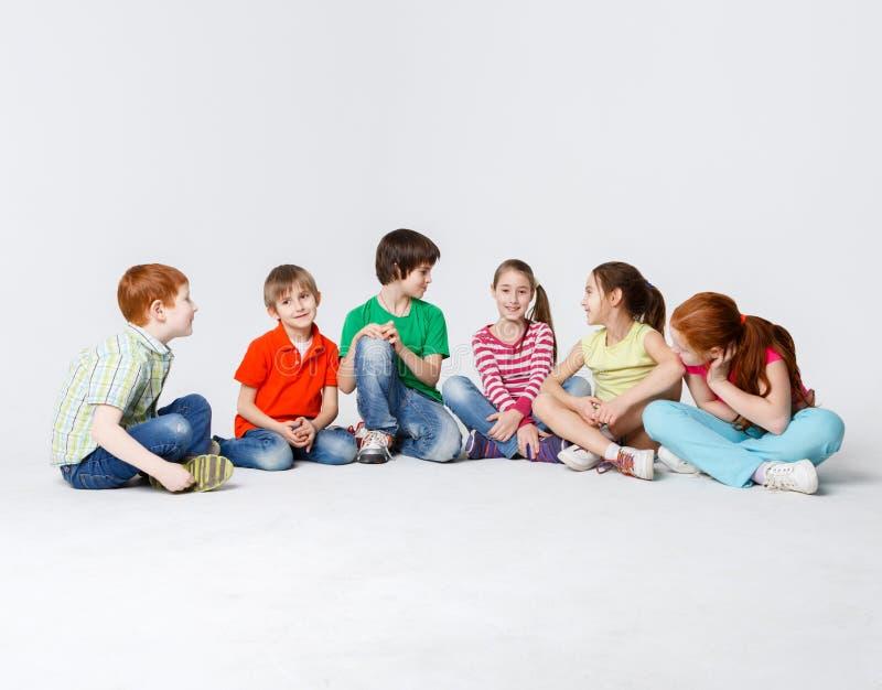 愉快的孩子坐地板在演播室,拷贝空间 免版税库存图片