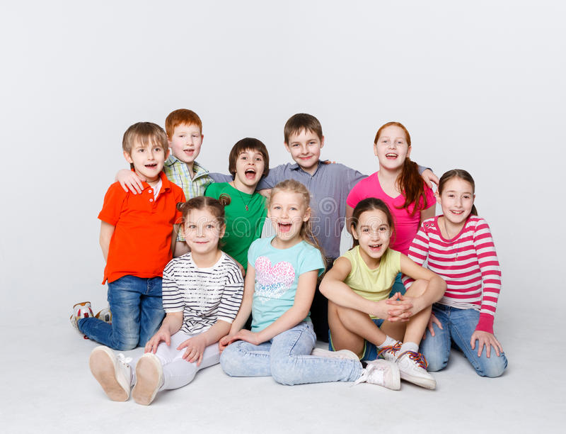 愉快的孩子坐地板在演播室,拷贝空间 图库摄影