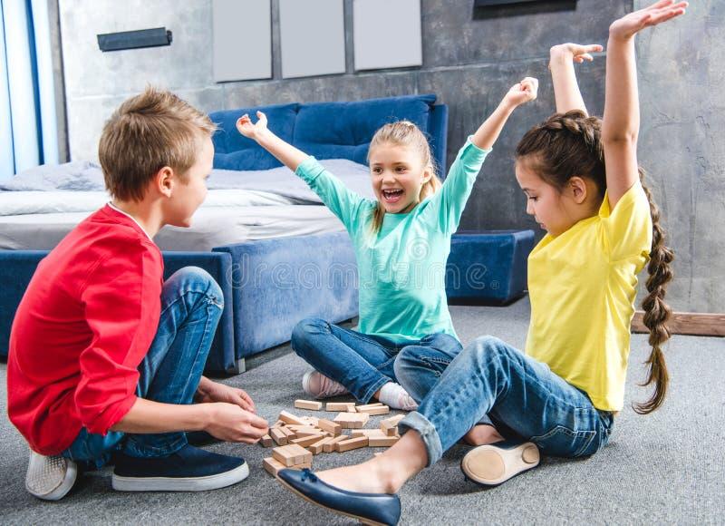 愉快的孩子坐地毯和使用 免版税图库摄影