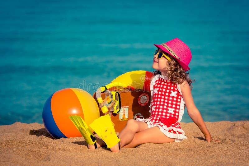 愉快的孩子坐海滩 免版税库存照片